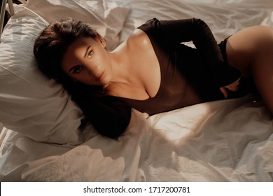 Portrait of a hot and graceful woman laying in a black leotard costume among bed sheets and holding her dark brown hair with hand