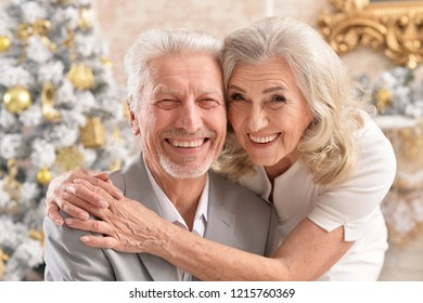 Portrait of a hugging senior couple with blurred Christmas decorations