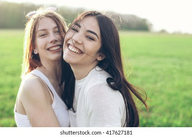Portrait of hugging and smiling two young women