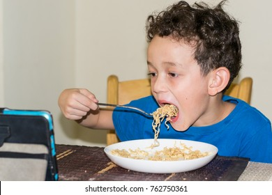 Portrait of a hungry boy eating noodles  while watching smart phone, boy eating noodles.