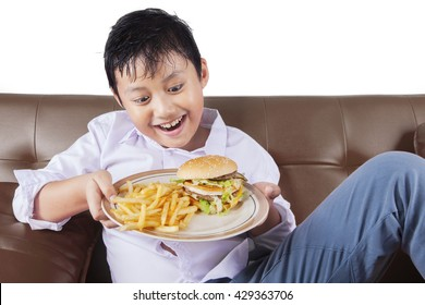 Portrait of hungry boy sitting on the sofa while holding a plate of hamburger and french fries