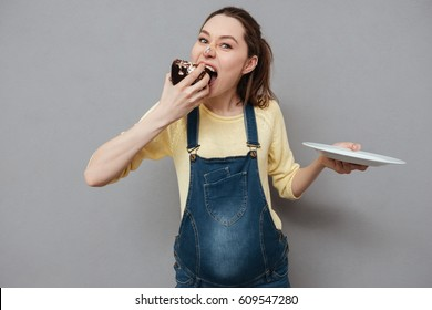 Portrait of a hungry pretty pregnant woman eating chocolate cake isolated on a gray background