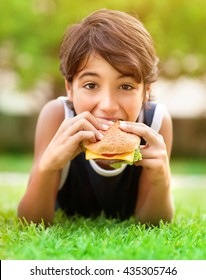 Portrait of a hungry teen boy lying down on fresh green grass and eating burger, enjoying picnic outdoors, summer holidays in the camp
