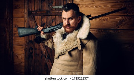 A portrait of a hunter man standing at the wooden house. Man, hunting, musket.