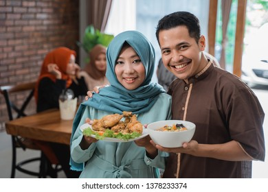 portrait of husband and wife serving food for friend and family for break fasting together during ramadan