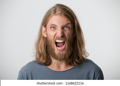 Portrait of hysterical irritated bearded young man with blonde long hair wears gray t shirt looks mad and shouting isolated over white background