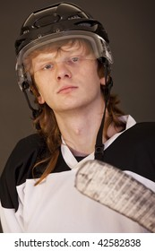 portrait of ice hockey player with stick over black
