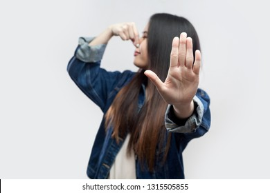 Portrait of ignoring brunette asian young woman in casual blue denim jacket with makeup standing pinching her nose and showing stop gesture hand. indoor studio shot, isolated on light grey background.