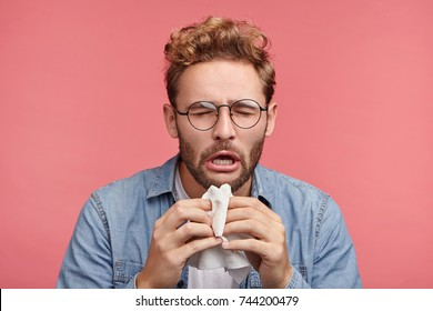 Portrait of ill or sick bearded male sneezes and coughs, uses handkerchief, rubs nose, being allergic to animals. Man has running nose, caught cold when had walk outdoors in winter or autumn