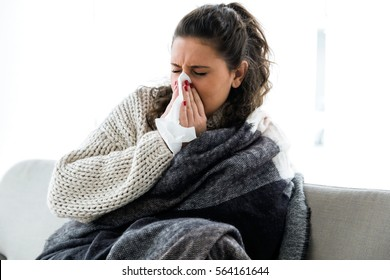 Portrait of illness young woman sneezing in a tissue.