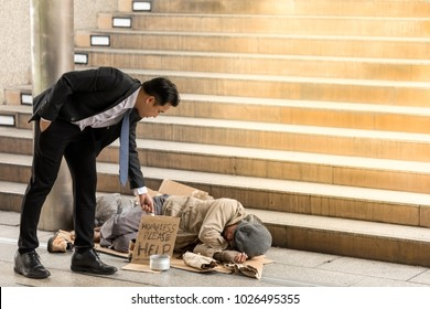 Portrait image of Asian 40s Businessmen's holding money gives money to an asian 50s mature homeless man is Sleeping. Senior person hands begging for money