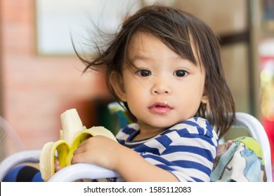 Portrait image of baby 1-2 years old. Happy Asian child girl enjoy eating a banana with sweet smiling. Food and healthy kids concept.