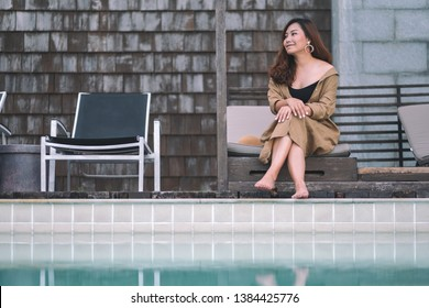 Portrait image of a beautiful asian woman enjoyed sitting by the swimming pool