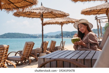 Portrait image of a beautiful young asian woman holding and drinking coconut juice on the beach