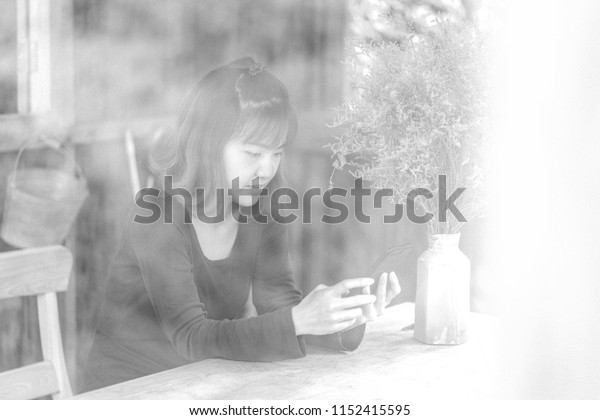 Portrait image of business woman working on her smart phone at the cafe. Blurred photo with grain effect, blurred background in mono tone. Concept for young freelance, new gen worker.