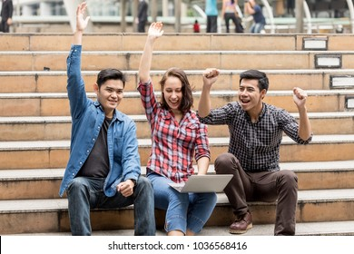 Portrait image of Happy euphoric success Two Asia students and one girl student after watching school record of them in laptop outside a classroom at international school successful concept
