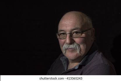 Portrait image of a mature man with glasses and a mustache. Taken on a black background with copy space