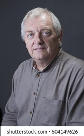 Portrait image of a mature man, looking into the camera. Taken on a grey background.