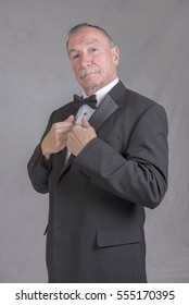 Portrait image of a mature man in a suit and bow tie, looking at the camera. Taken on a grey background. Vertical image.