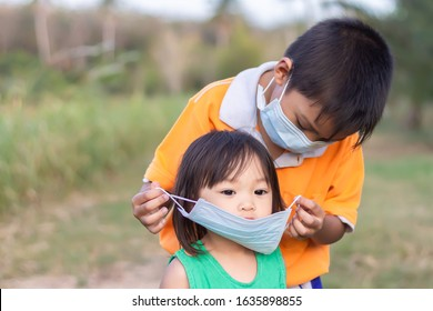 Soft focus. Portrait image of young Asian child brother wearing medical mask protection for his little baby sister. Children wearing mask for preventive the Corona 's virus (covid-19) disease.