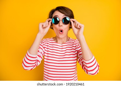 Portrait of impressed brunette lady wear spectacles red shirt isolated on orange color background