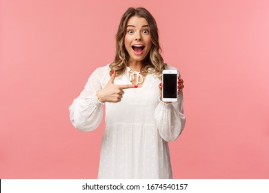 Portrait of impressed, excited young blond woman showing something awesome on display, pointing mobile phone screen and smiling astonished, brag with her recent match on dating app