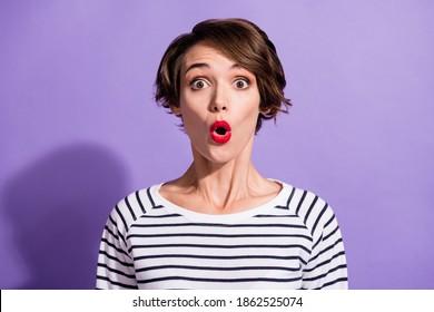 Portrait of impressed funny short brunette hairdo girl wear stripped pullover isolated on violet color background