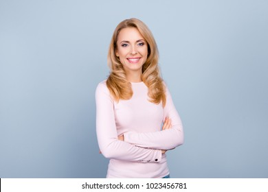 Portrait of independent, pretty, cute, nice woman with modern hairstyle having her arms crossed, looking at camera, standing over grey background