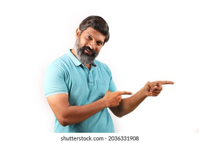 Portrait of an Indian bearded man wearing shirt showing thumbs up and pointing fingers. Funky expressions white background. Man full of confidence.