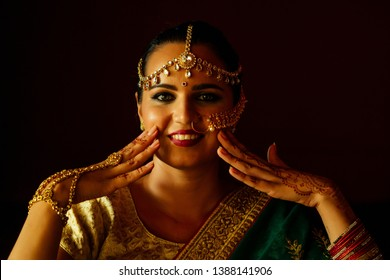 portrait indian beautiful female in golden rich jewelery and tradition saree face closeup professional make-up wearing bindi on head .Muslim Woman face portrait with bindis maang tikka ,nath,nose Pin