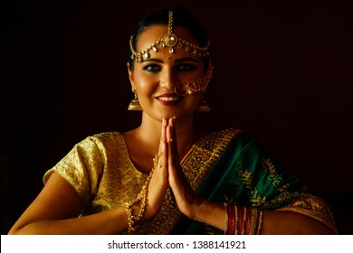 portrait indian beautiful female in golden rich jewelery and tradition saree professional make-up wearing bindi on head .Muslim Woman face portrait with bindis maang tikka ,nath,nose Pin welcoming