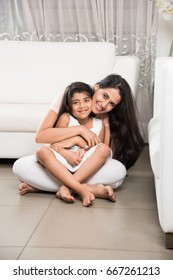 Portrait of an Indian beautiful small girl or daughter sitting on mother's lap on floor, while mother holding her tightly with both arms, selective focus