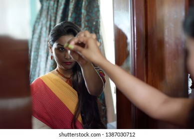 Portrait of an Indian Bengali beautiful and young girl in Indian traditional ethnic dress sari applying bindi to her forehead while doing makeup in front of a mirror. Indian fashion and portrait
