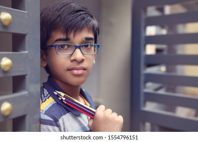 Portrait of Indian boy posing to camera with drawing pencil