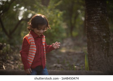 Portrait of an Indian brunette baby boy in winter wear enjoying himself in a field on a winter afternoon in green natural background. Indian lifestyle and childhood.