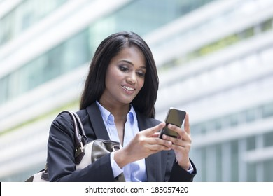 Portrait of an Indian businesswoman standing outside using mobile phone to send a message