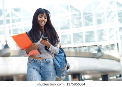 Portrait of Indian female university student walking in the city with mobile phone