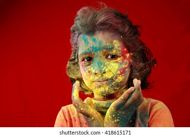 Portrait of an Indian girl with face smeared with colored powder in a red background. Concept for Indian festival Holi.