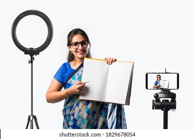 Portrait of Indian lady teacher in saree stands against green, white or blackboard , conducting online class using Camera, internet and lights