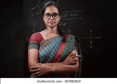 Portrait of Indian lady teacher stands in front of a blackboard