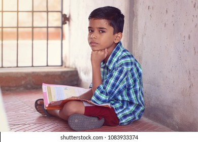Portrait of Indian Little Boy Posing to Camera with Textbook