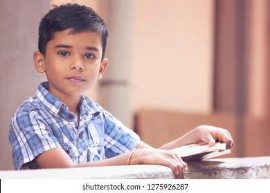 Portrait of Indian little boy posing to camera with school text book