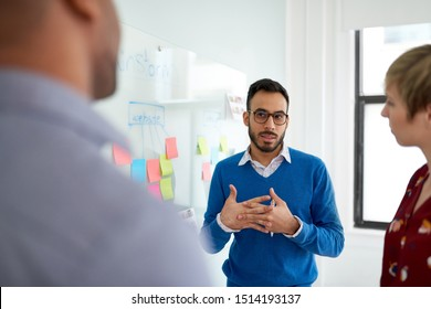Portrait of an indian man in a diverse team of creative millennial coworkers in a startup brainstorming ideas