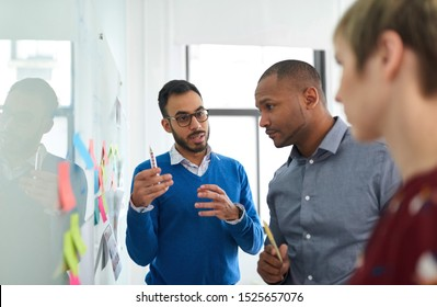 Portrait of an indian man in a diverse team of creative millennial coworkers in a startup brainstorming strategies