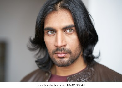 Portrait of Indian man with long black hair in studio