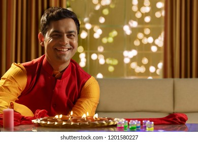 Portrait Of Indian Man Sitting Indoors with diyas on the occasion of Diwali