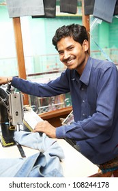 Portrait of indian man tailor at work place with sewing machine