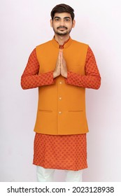 A portrait of a indian man in a traditional wear in welcome gesture pose - Namaste.