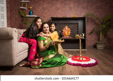 portrait of Indian Mother and daughter with puja thali in traditional wear on ganesh festival