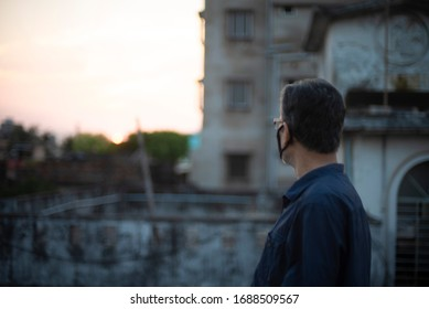 Portrait of an Indian old man wearing corona preventive mask on a rooftop  in home isolation.Indian lifestyle, disease and home quarantine. - Shutterstock ID 1688509567